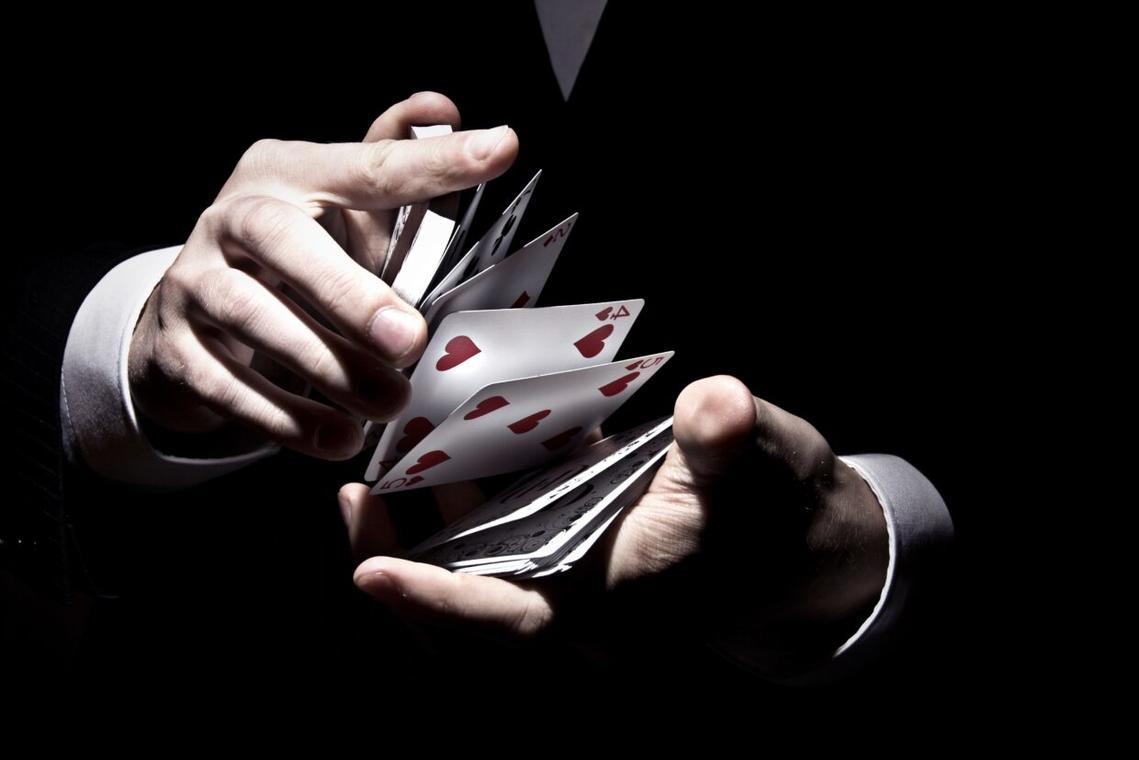 magician-shuffling-the-cards-in-cool-way-under-the-spotlight-1240x827