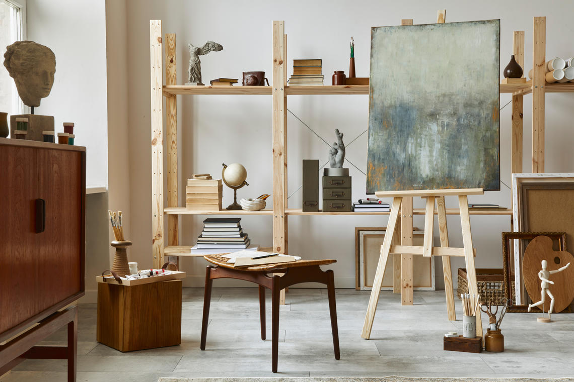 Unique artist workspace interior with stylish teak commode, wooden easel, bookcase, artworks, painting accessories, decoration and elegant personal stuff. Modern work room for artist. Template.
